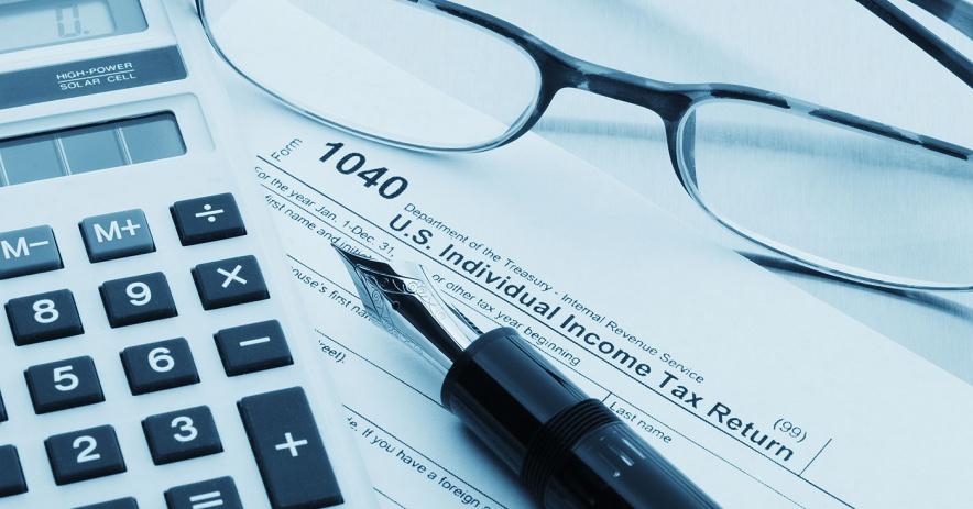Formulario de impuestos 1040 con calculator, vasos y pluma estilográfica.