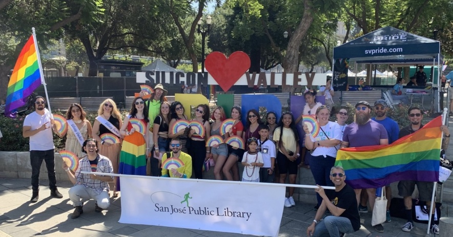 Large group of San Jose Public Library staff members smiling, celebrating, and carrying rainbow flags and fans at the Silicon Valley LGBTQIA+ Pride Festival.