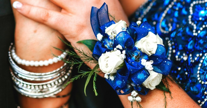 Close up of hands wearing a blue corsage and blue prom dress.