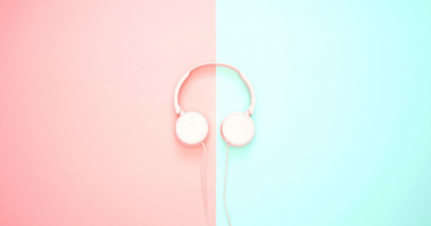 Pink headphones sitting on a pink and blue background.