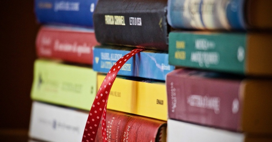 Stack of books with a red ribbon between two of them.