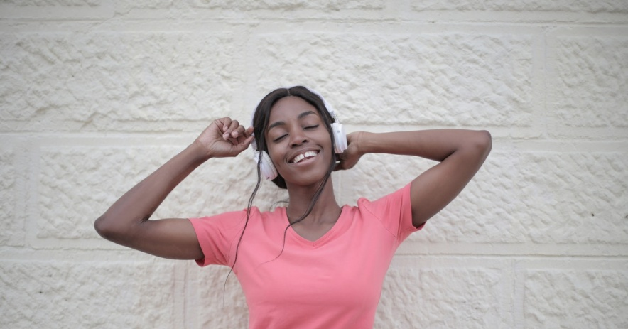 Young black woman wearing a pink shirt, smiling and dancing while wearing headphones.