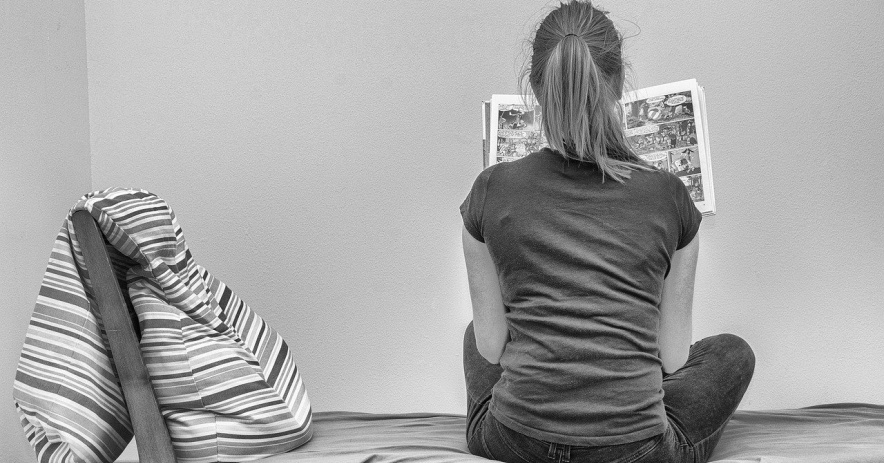 A reader is reading a graphic novel on a bed, sitting with her back to the camera.