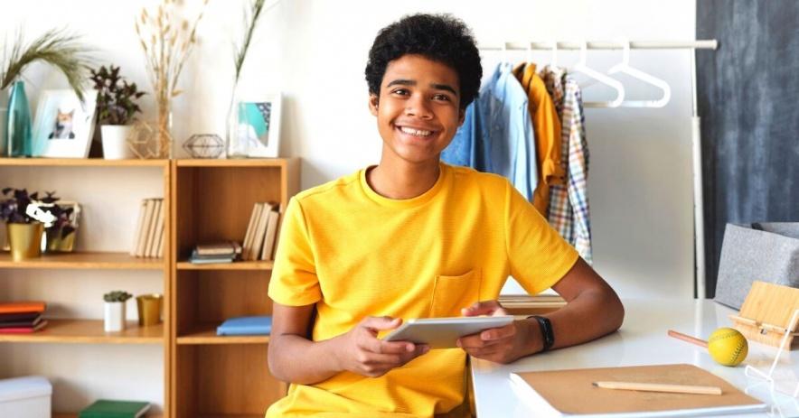 Niño con camiseta amarilla con cuello redondo sentado en una silla
