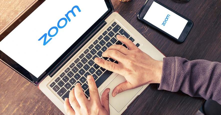 Las manos escriben en una computadora portátil que muestra Zoom en la pantalla.