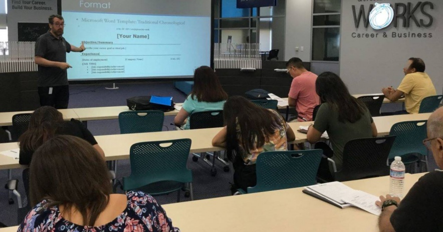 John Savercool teaches a class of students who are facing a screen about formatting in San Jose Public Library Works classroom.