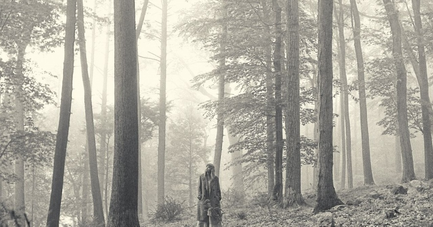 A black and white photo of Taylor Swift standing in a forest.