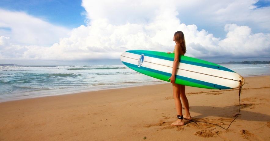 cô gái trên bãi biển cầm ván lướt sóng