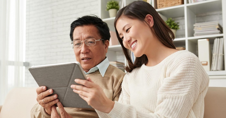 Woman sitting on sofa with her senior dad explaining to him how use a digital tablet.