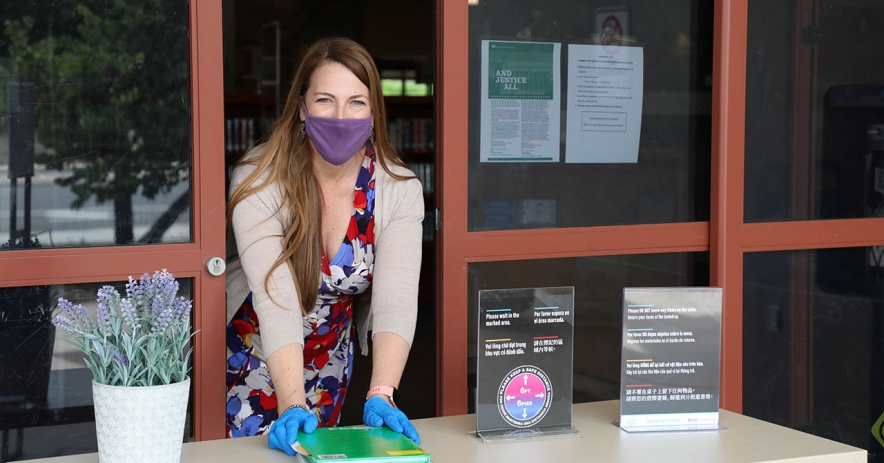 Library staff member with face mask places books on the express pickup table.