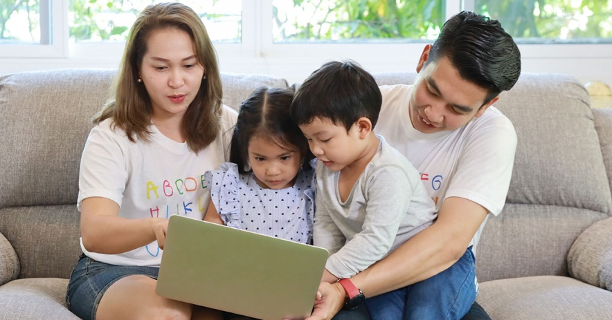 Mother and father with young son and daughter using laptop.