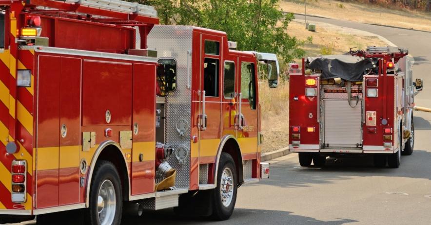 Hai chiếc xe cứu hỏa chạy trên con đường trải nhựa ở một vùng nông thôn khô cằn.