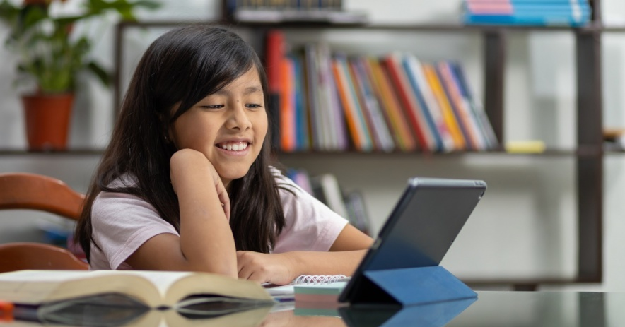 Student smiling while learning on a tablet device.