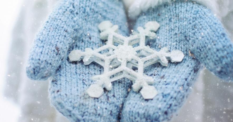 Manos con guantes azules sosteniendo un copo de nieve