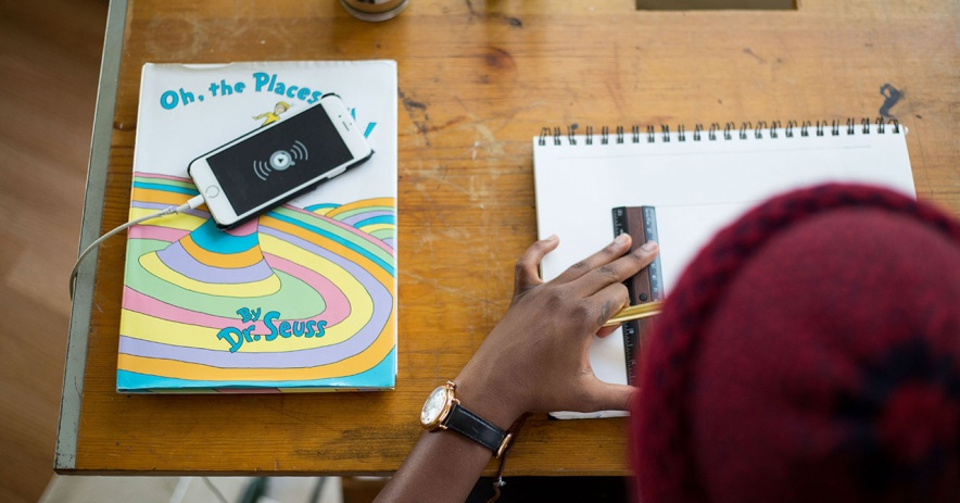 Student measuring in a sketchbook. The book, 'Oh, the Places You'll Go' sits next to them on the desk. Image Credit: Photo by Tamarcus Brown on Unsplash