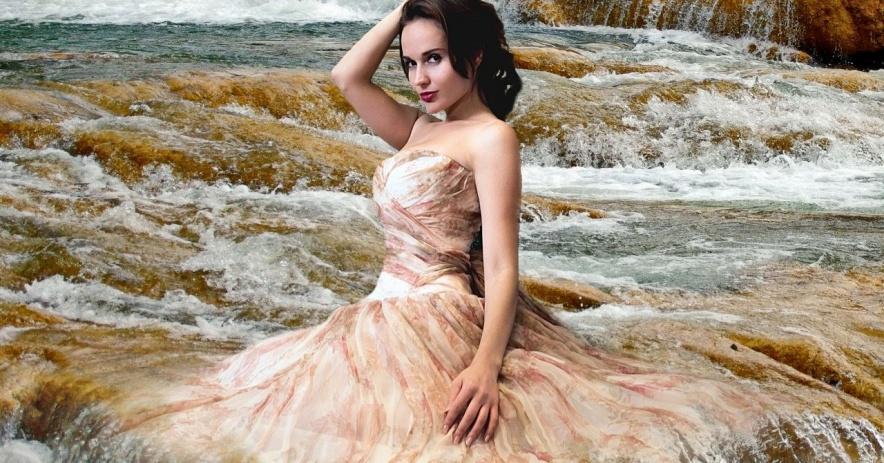 Mujer en agua con un vestido en cascada en una cascada