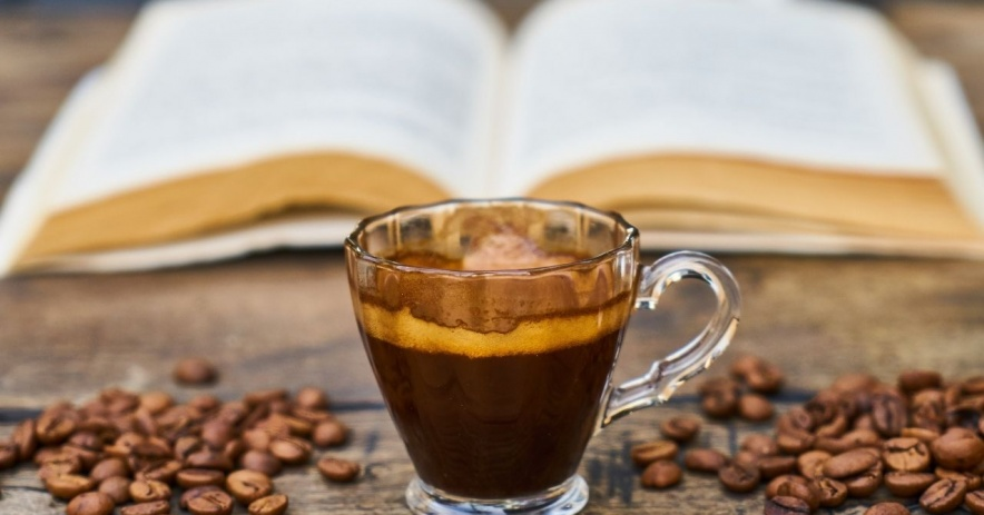Cup of espresso surrounded by beans with a book in the background