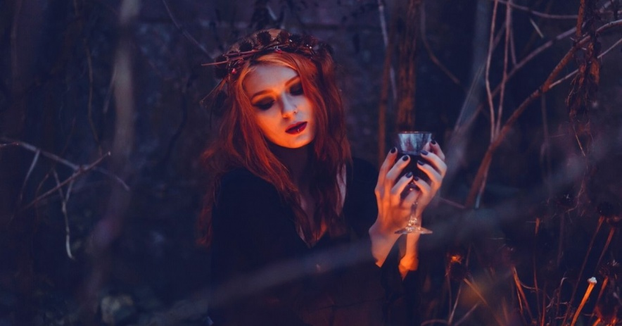 A witchy looking woman in a forest holding a goblet