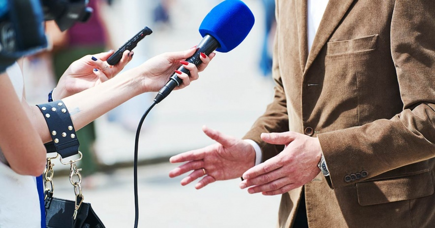 News reporter holding microphone towards a speaker.