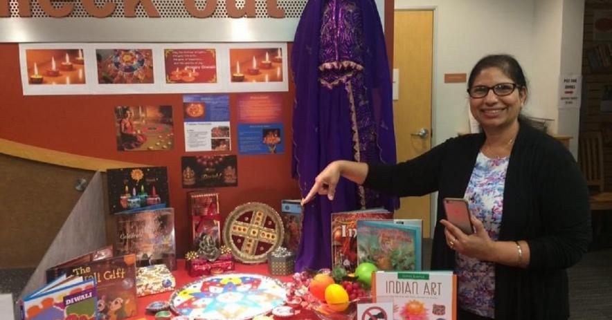 La mujer señala con orgullo una exhibición de Diwali que instaló en la biblioteca.