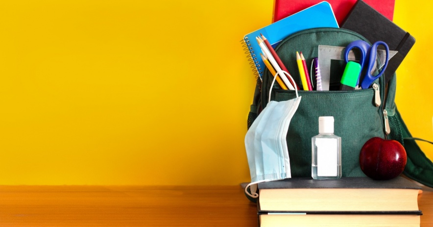 Mochila con útiles escolares, mascarilla, desinfectante de manos, libros y una manzana.