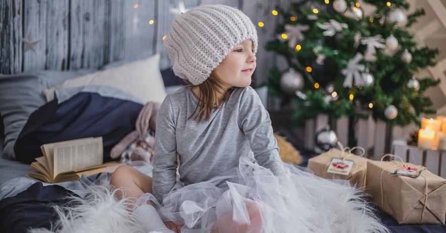Niña en traje de invierno se sienta en la cama con libros y regalos. Un árbol de Navidad está al fondo.