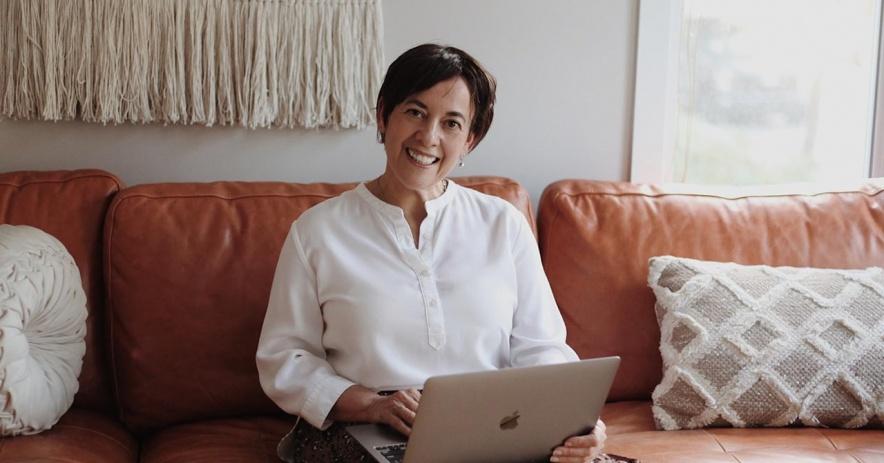 Mujer sentada en un sofá con un portátil.