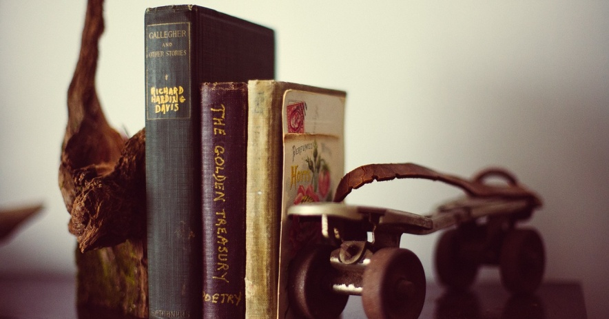 Three books held up between a rollerskate and a piece of wood.