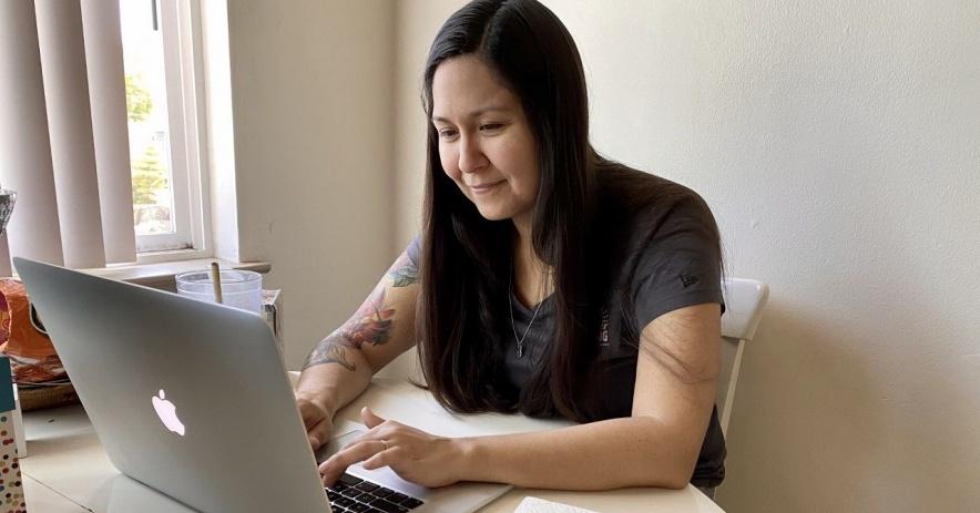 Mujer en casa en portátil.