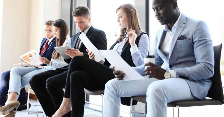 Los solicitantes de empleo sentados revisan sus hojas de vida mientras esperan una entrevista.