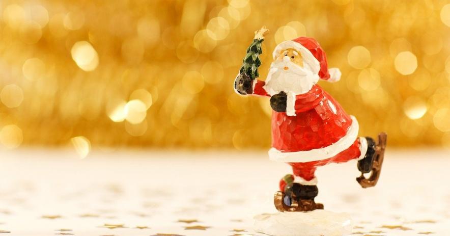 Clay Santa sosteniendo un árbol y patinando.