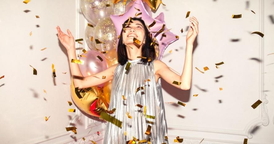 Mujer con un vestido plateado de pie frente a globos con las manos en alto sonriendo mientras cae confeti dorado.