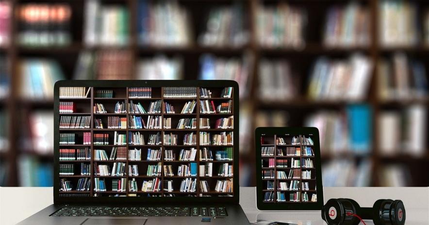Imagen de una computadora portátil, un eReader y auriculares frente a los estantes de la biblioteca llenos de libros.