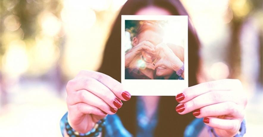 Adolescente sosteniendo una polaroid con una pareja haciendo un corazón con sus manos.