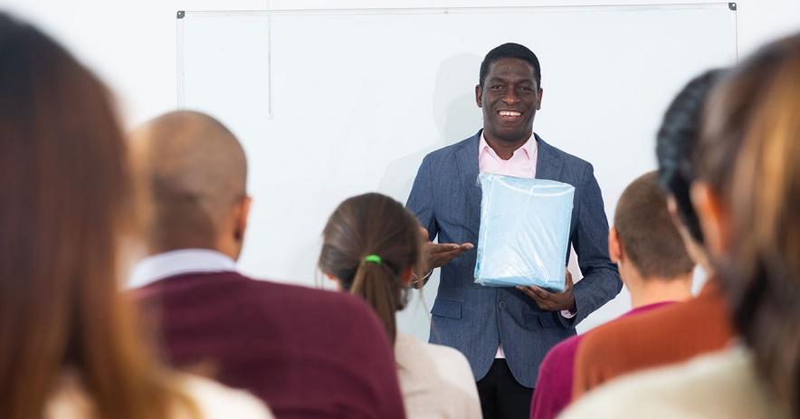 Instructor hablando frente a una clase de estudiantes adultos