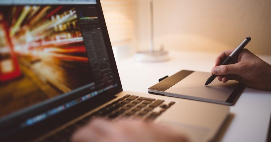 Imagen de una persona que trabaja en una computadora portátil y toma notas