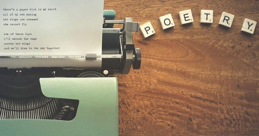 Una máquina de escribir con un papel con poesía escrita y letras de scrabble deletreando la palabra poesía.