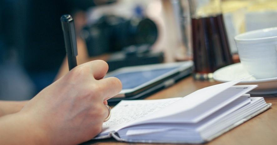 Persona que escribe en un cuaderno con una taza de café y una computadora portátil en el fondo.