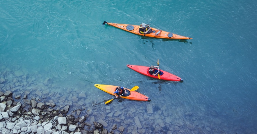 Grupo de niños en canoas en un lago azul claro