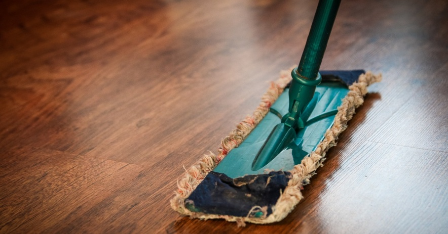 Green swiffer with a reusable pad cleans a hardwood floor.