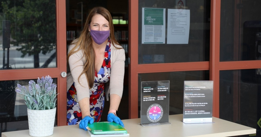 Staff member wearing mask and gloves places books on the Express Pickup table outside the library.