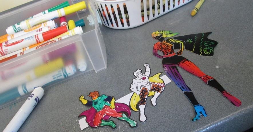 Tres superhéroes coloreados con crayones y marcadores.