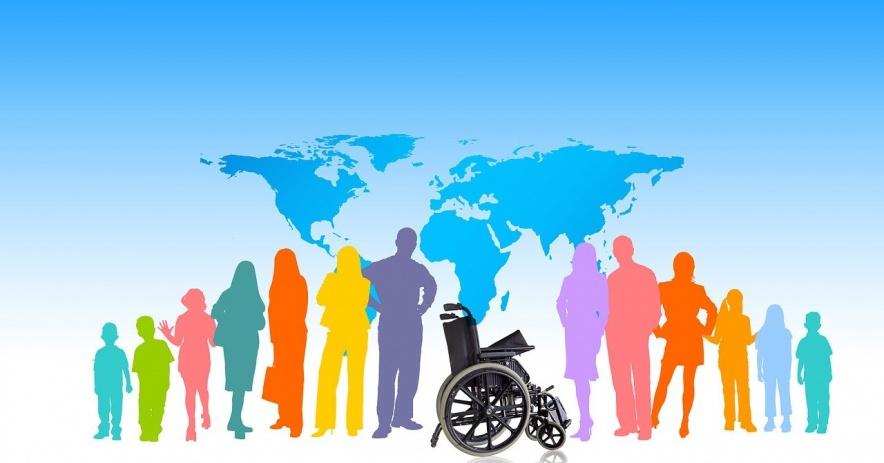 Personas de diferentes colores frente a un mapa del mundo con una silla de ruedas en el medio.