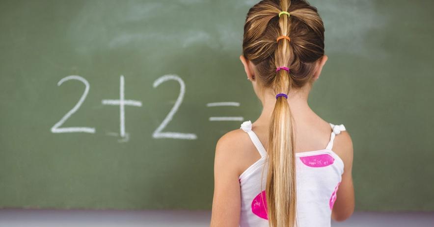 Cô gái viết '2 + 2' trên bảng đen