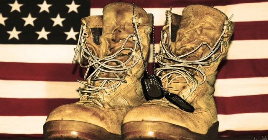 Combat boots, dog tags and the flag of the United States