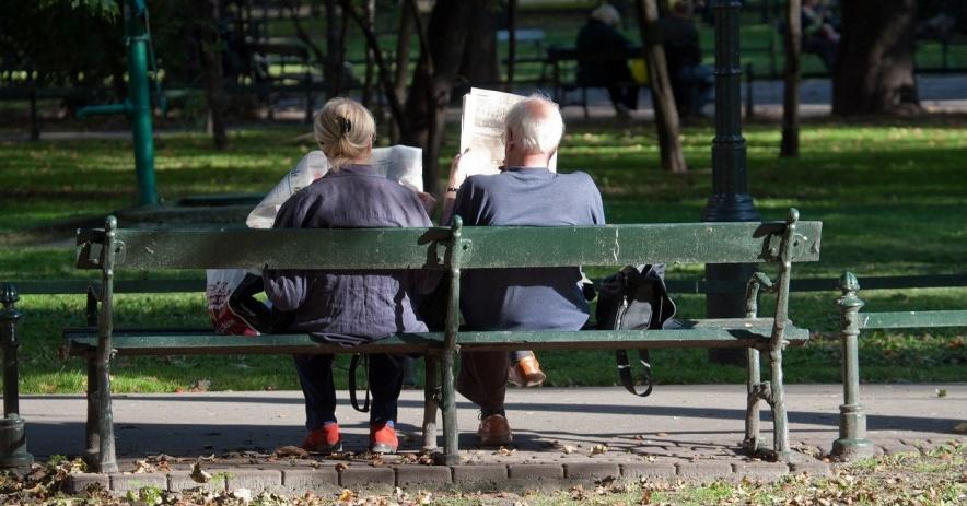 Imagen de la parte de atrás de dos personas sentadas en un banco del parque leyendo periódicos
