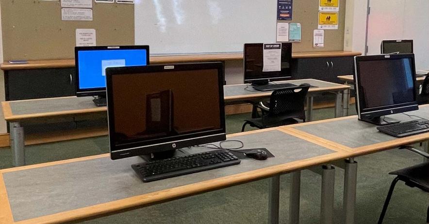 Centro tecnológico con estaciones de computadoras socialmente distanciadas en escritorios.