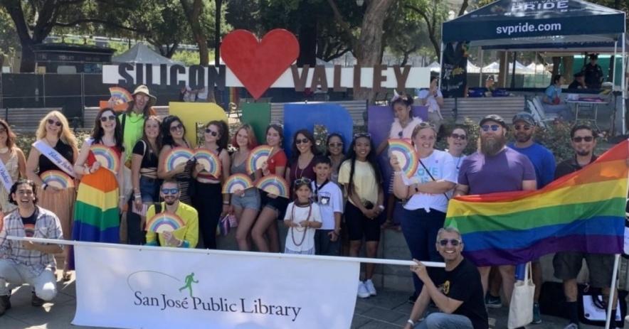 Fotografía de un gran grupo de personas volando, vistiendo y mostrando banderas del arco iris y sosteniendo una pancarta blanca leyendo San Jose Public Library.