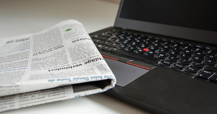 Imagen de un periódico y una computadora portátil