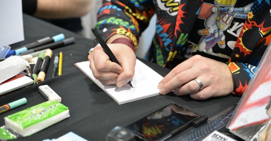 dibujante de cómic en la mesa con herramientas de arte.